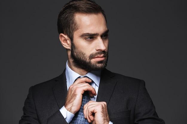 Zbliżenie przystojny młody człowiek biznesu ubrany w garnitur stojący na białym tle, odwracając się