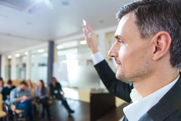 Zbliżenie przystojny poważny mówca stojący z podniesioną ręką na spotkaniu biznesowym w sali konferencyjnej