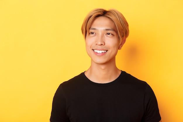 Zbliżenie przystojny stylowy koreański facet z jasnymi włosami, wyglądający rozmarzonym i pełnym nadziei w lewym górnym rogu, uśmiechnięty zadowolony, stojący żółta ściana