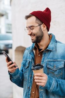 Zbliżenie przystojny szczęśliwy młody stylowy brodaty mężczyzna spacerujący na świeżym powietrzu na ulicy, trzymający filiżankę kawy na wynos, przy użyciu telefonu komórkowego