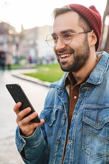 Zbliżenie przystojny szczęśliwy młody stylowy brodaty mężczyzna spacerujący na zewnątrz na ulicy, przy użyciu telefonu komórkowego