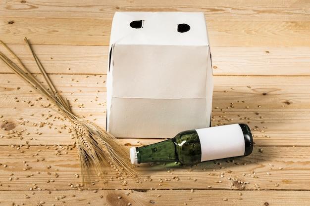 Zbliżenie pudełka kartonowego; zielona butelka piwa i kłosy pszenicy na drewniane tło