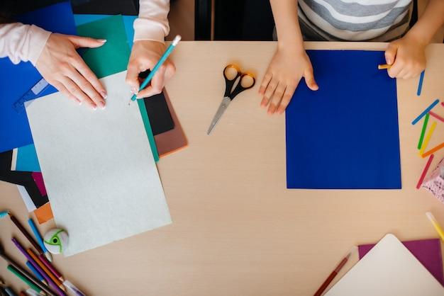 Zbliżenie pulpitu, na którym odrabiam zadanie domowe ucznia z matką. badanie.