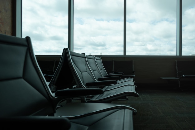 Zbliżenie: pusty poczekalnia na lotnisku, okna z chmurami, miejsce.