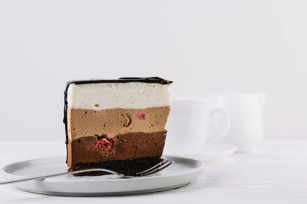 Zbliżenie pyszne ciasto i widelec serwowane w tablicy