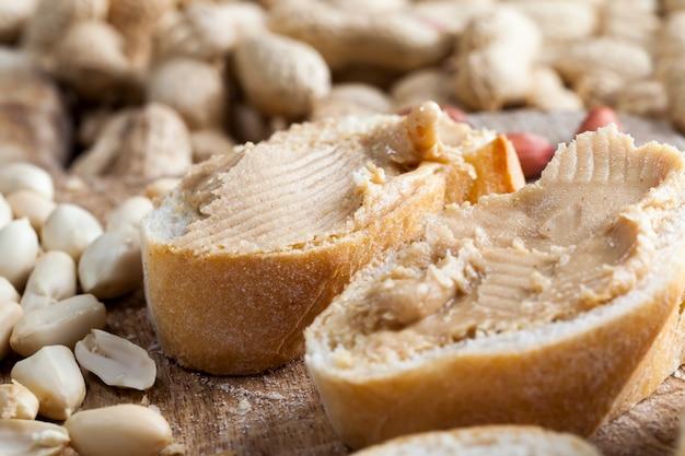 Zbliżenie pyszne masło orzechowe i biały chleb na stole, składniki do przygotowania szybkiego śniadania chleba i orzeszków ziemnych, pasta orzechowa pieczone orzeszki ziemne