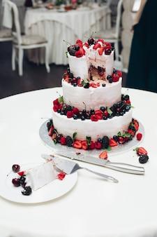 Zbliżenie pyszne słodkie tort weselny ozdobiony świeżymi truskawkami, jagodami i jeżynami. pokrojony tort weselny w zbliżeniu.