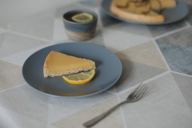 Zbliżenie pyszne tarta cytrynowa z zestawem do herbaty i cytrynami