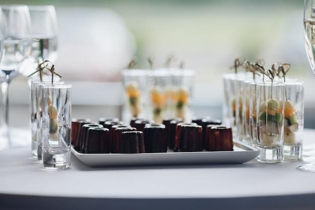 Zbliżenie pyszne zdrowe przekąski serwowane na przyjęcie urodzinowe. selektywne skupienie słodkich bananów, kiwi i pomarańczy w okularach. koncepcja cateringu, deserów, aranżacji i dekoracji.