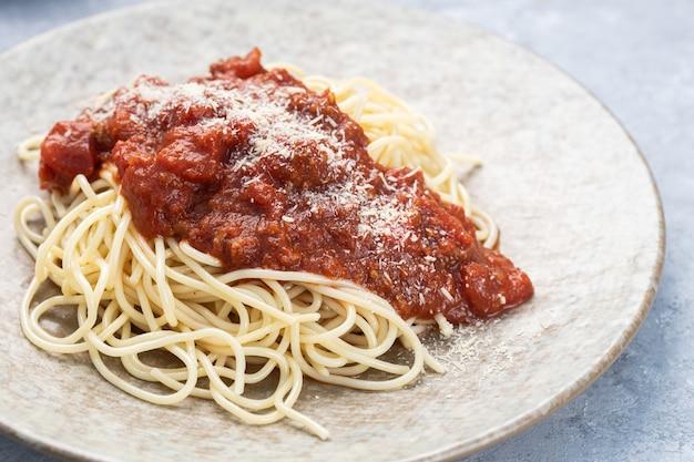 Zbliżenie pysznego makaronu z sosem pomidorowym i tartym serem na talerzu