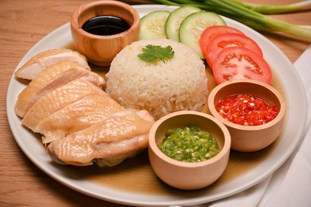 Zbliżenie pysznego ryżu z kurczaka hajnańskiego podawanego z pysznymi sosami chili z kurczaka na parze