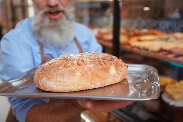 Zbliżenie pysznego świeżo upieczonego chleba na tacy w rękach starszego piekarza brodaty