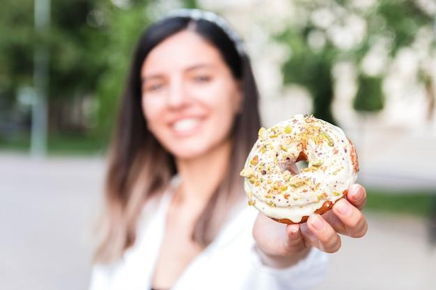 Zbliżenie pyszny i kolorowy pączek w ręce kobiety nieostre w parku miejskim. śmieciowy słodki i smaczny deser typu fast food