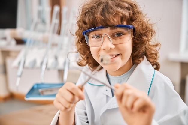 Zbliżenie radosnego dziecka w fartuchu laboratoryjnym trzymającego narzędzia dentystyczne podczas pozowanie w gabinecie dentystycznym