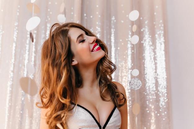 Zbliżenie radosnej europejskiej dziewczyny z lśniącymi ciemnymi włosami pozuje z zamkniętymi oczami i natchnionym uśmiechem. romantyczna kobieta w białej sukni stojącej na imprezie.