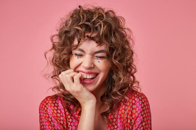 Zbliżenie radosnej kobiety z lokami, śmiejącej się z czegoś z zamkniętymi oczami, dotykającej twarzy ręką, stojącej. koncepcja pozytywnych emocji