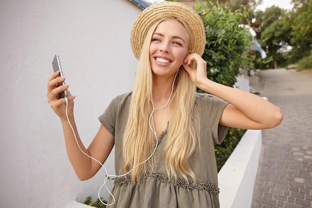 Zbliżenie radosnej ładnej pani wkładającej słuchawki, słuchającej muzyki na swoim smartfonie, ubrana w swobodną lnianą sukienkę i słomkowy kapelusz
