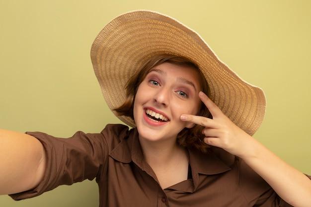 Zbliżenie radosnej młodej blondynki robi znak pokoju wyciągając rękę w kierunku kamery