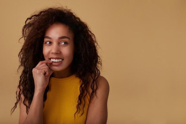Zbliżenie radosnej młodej uroczej ciemnoskórej brunetki kręconej pani trzyma palec wskazujący na jej dolnej wardze, patrząc wesoło na bok, odizolowane na beżowym tle