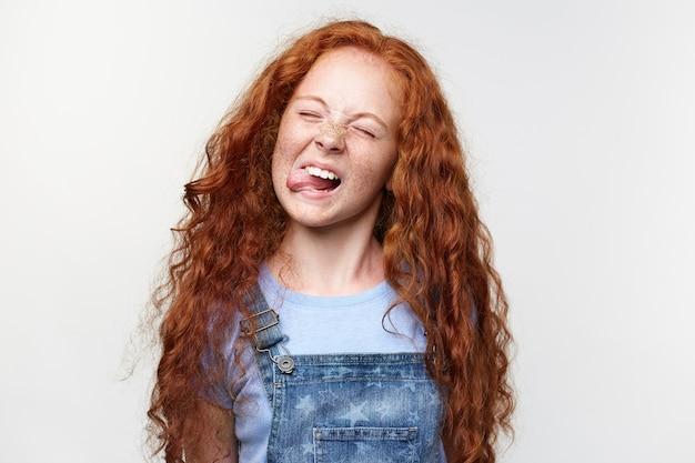Zbliżenie radosnej ślicznej dziewczynki z rudymi włosami i piegami, pokazuje język w aparacie i wygląda śmiesznie, stoi na białym tle z zamkniętymi oczami.