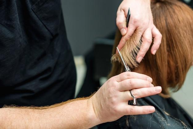 Zbliżenie rąk fryzjera tną włosy klienta w salonie.