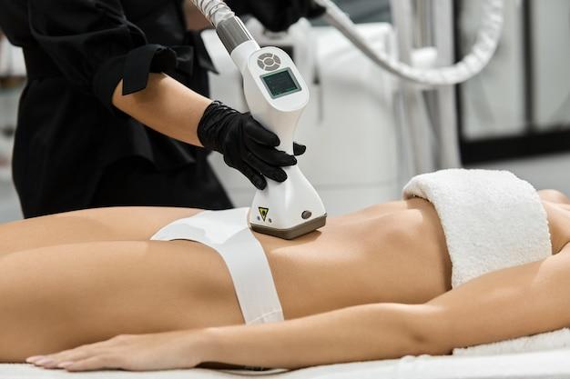 Zbliżenie: ramię masażysty za pomocą masażera lpg na brzuchu kobiety