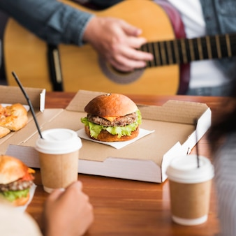 Zbliżenie ręce gra na gitarze przy stole