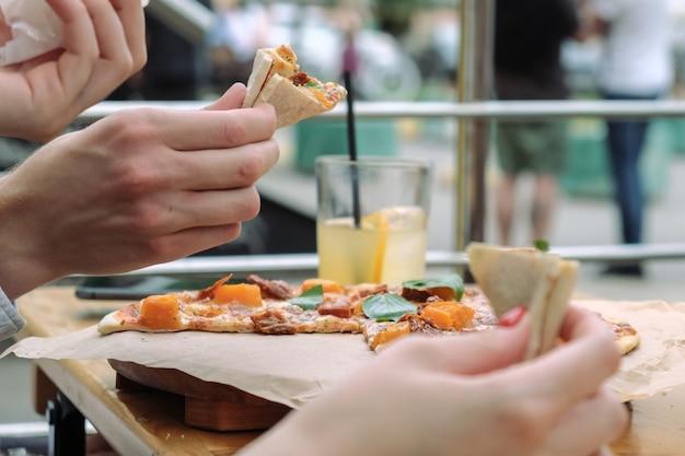 Zbliżenie: ręce i pizza z liśćmi bazylii w kawiarni na świeżym powietrzu. ludzie jedzą pizzę rękami. na stole jest lemoniada w szklance.