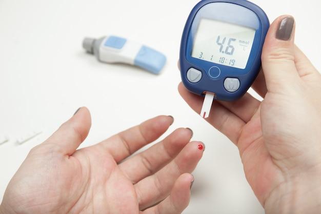 Zbliżenie ręce kobiety badanie wysokiego cukru we krwi z glukometrem