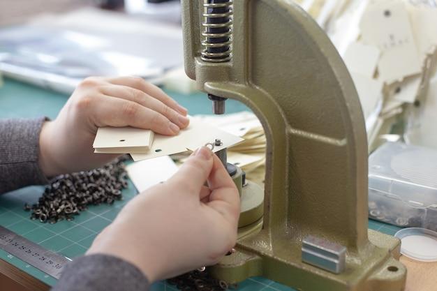 Zbliżenie ręce mężczyzna umieścić przelotki i oczko w stosie pustych tagów odzieżowych na dużej ręcznej prasie profesjonalnej maszyny do przelotek