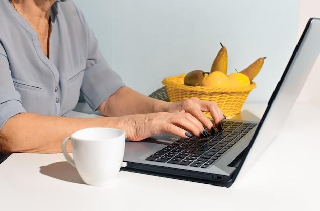 Zbliżenie ręce starsza kobieta wpisując na laptopie
