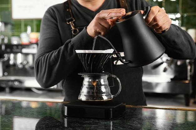 Zbliżenie ręce trzymając czajnik z wodą