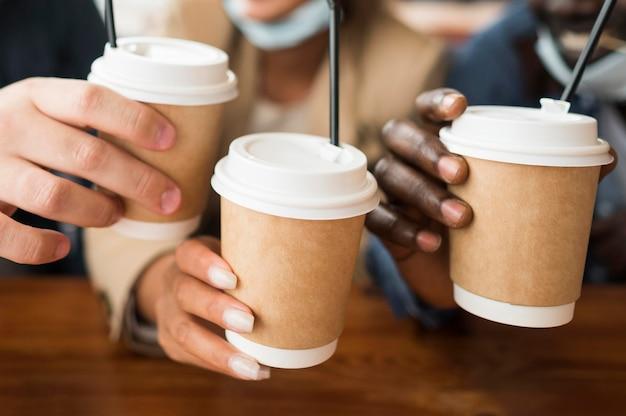 Zbliżenie ręce trzymając filiżanki do kawy