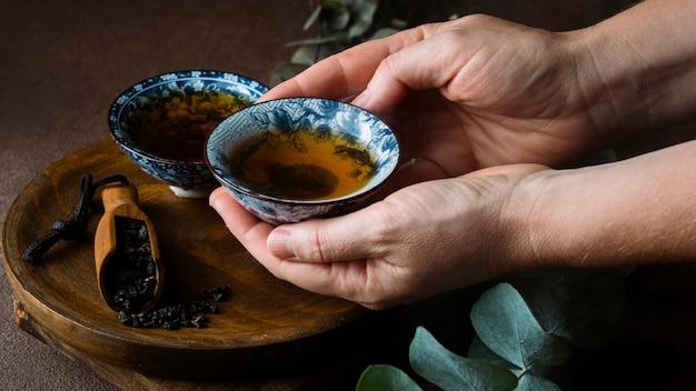 Zbliżenie ręce trzymając kubek herbaty