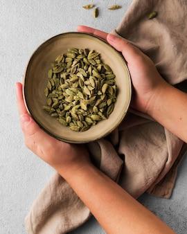 Zbliżenie ręce trzymając miskę nasion