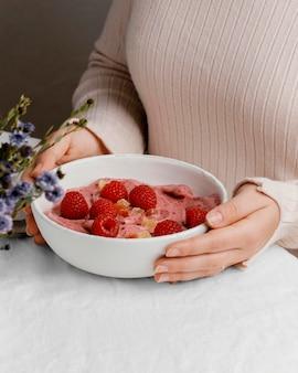 Zbliżenie ręce trzymając miskę ze śniadaniem
