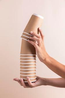 Zbliżenie ręce trzymając papierowe kubki