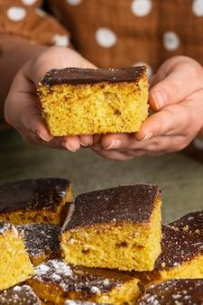 Zbliżenie ręce trzymając pyszne ciasto