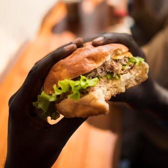 Zbliżenie ręce trzymając pysznego burgera