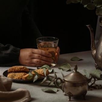 Zbliżenie ręce trzymając szklankę herbaty