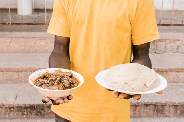 Zbliżenie ręce trzymając talerze z jedzeniem