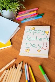Zbliżenie ręcznie robionej karty dzień ojca z żółtymi sercami i kolorowymi ołówkami i pisakami na drewnianym stole z doniczkową rośliną i zeszytami