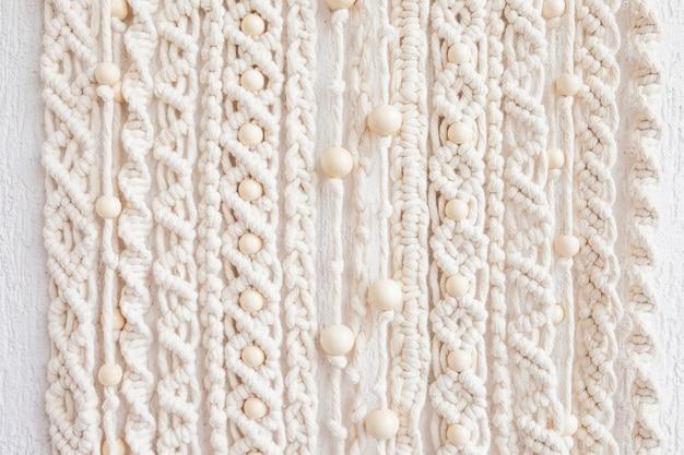 Zbliżenie: ręcznie robiony wzór tekstury makramy. ekologiczna nowoczesna dzianina. naturalna koncepcja dekoracji wnętrza.