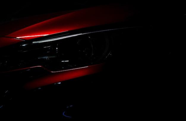 Zbliżenie reflektor błyszczący czerwony luksusowy suv samochód kompaktowy. elegancka technologia samochodów elektrycznych