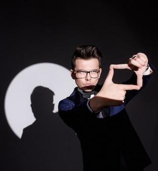 Zbliżenie reflektora pada na młodego mężczyznę, który pokazuje gest