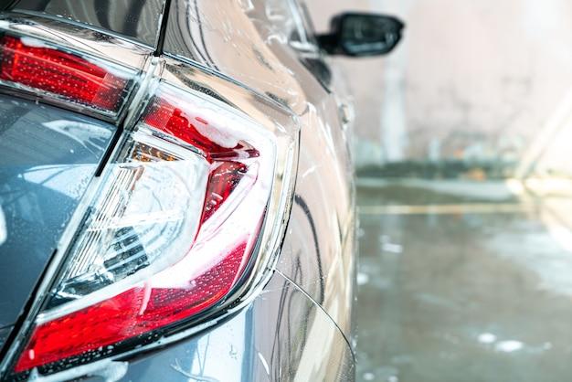 Zbliżenie reflektora samochodowego z pianką do mycia samochodu