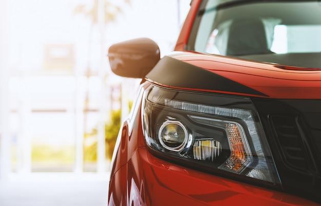 Zbliżenie reflektoru czerwony samochód z miękką ostrością i nadmiernym światłem w tle