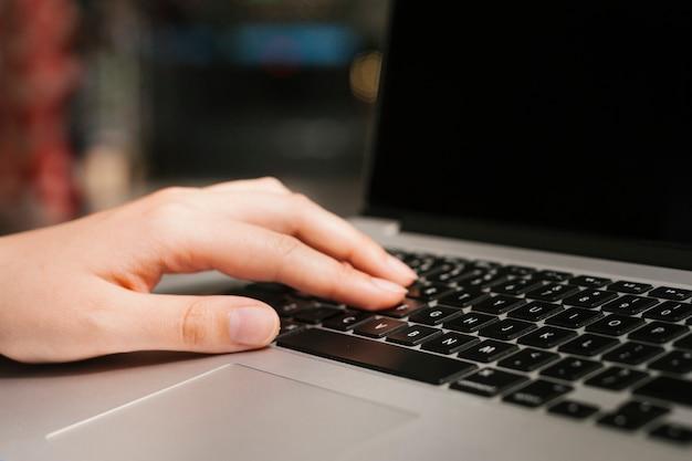 Zbliżenie ręka na laptop klawiaturze