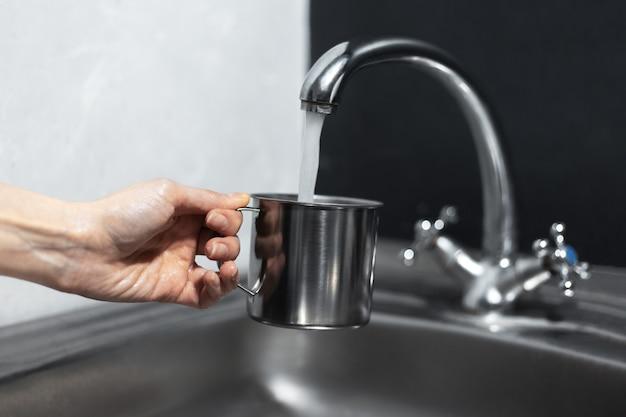 Zbliżenie: ręka trzyma kubek stalowy pod kranem w kuchni