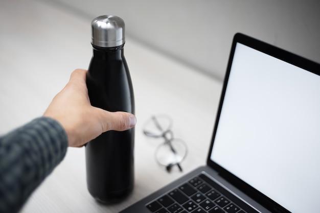 Zbliżenie: ręka trzyma stalową butelkę termiczną eco do wody na biurku